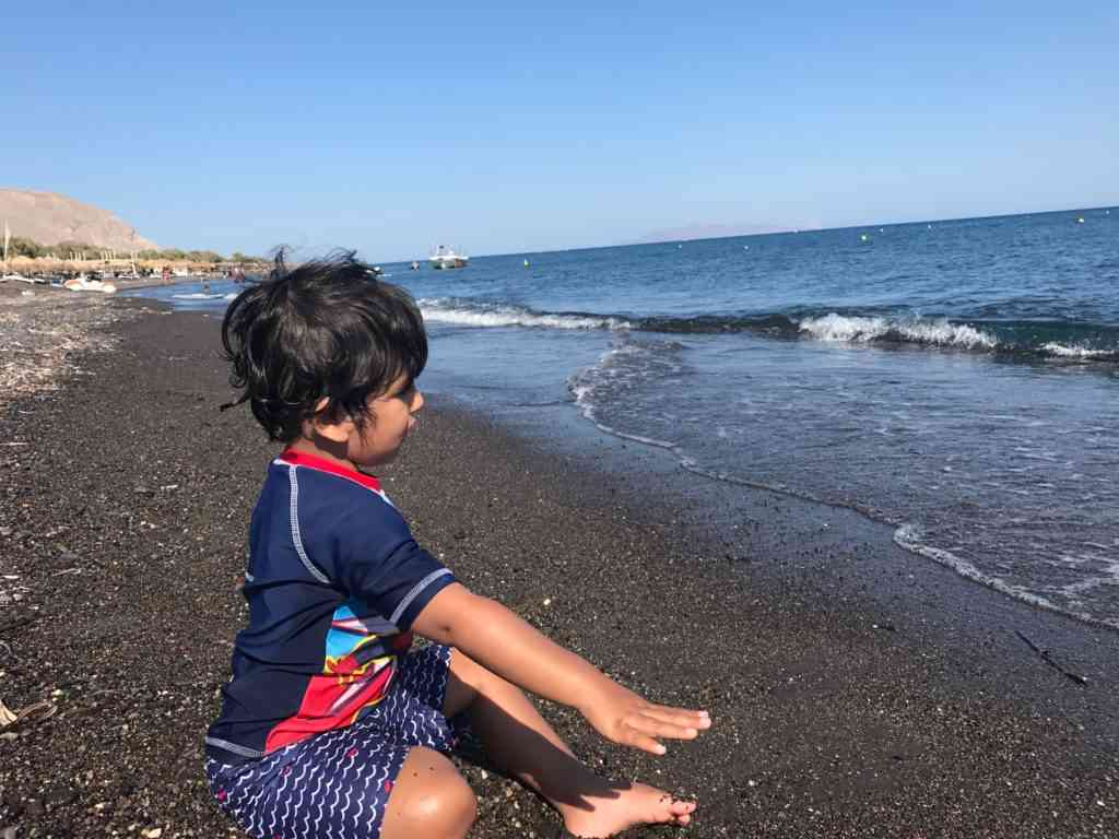 Aarav enjoying the amazing black sand beaches of Santorini