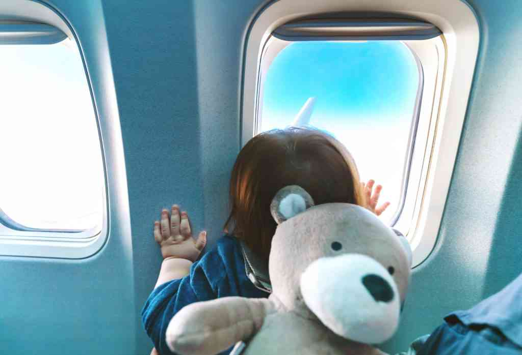little girl looking out of airplane window